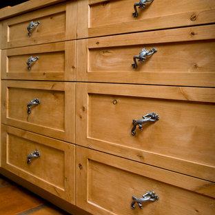 Diseño de armario y vestidor unisex, bohemio, con armarios estilo shaker, puertas de armario de madera clara y suelo de baldosas de terracota