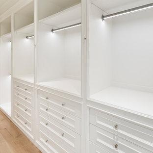 Klassisk inredning av ett stort walk-in-closet för könsneutrala, med vita skåp, ljust trägolv och luckor med infälld panel
