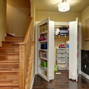 Imagen de armario unisex, clásico renovado, de tamaño medio, con armarios abiertos, puertas de armario blancas, suelo de madera oscura y suelo marrón
