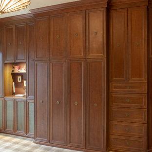 Klassisches Ankleidezimmer mit Ankleidebereich, Schrankfronten mit vertiefter Füllung, hellbraunen Holzschränken, Teppichboden und buntem Boden in New York