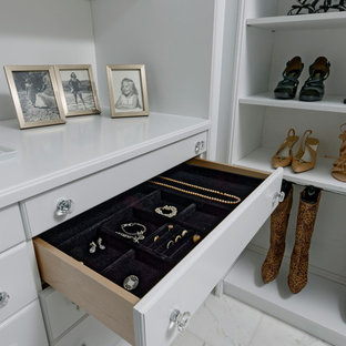 Example of a large transitional gender-neutral marble floor and white floor walk-in closet design in DC Metro with raised-panel cabinets and white cabinets