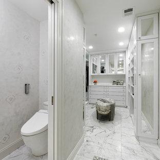 Foto di una grande cabina armadio unisex chic con ante con bugna sagomata, ante bianche, pavimento in marmo e pavimento grigio