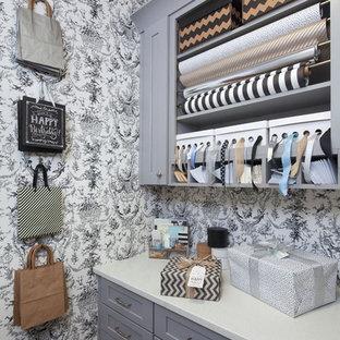 Diseño de armario y vestidor tradicional renovado, pequeño, con armarios con paneles empotrados, puertas de armario grises y suelo de madera oscura