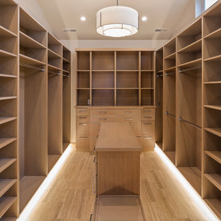 Inspiration for a medium sized traditional walk-in wardrobe for women in Seattle with flat-panel cabinets, light wood cabinets, travertine flooring and beige floors.