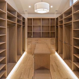 Ejemplo de armario vestidor de mujer, clásico renovado, de tamaño medio, con armarios con paneles lisos, puertas de armario de madera clara, suelo de travertino y suelo beige