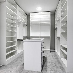 Idée de décoration pour un grand dressing champêtre neutre avec moquette, un placard sans porte, des portes de placard blanches et un sol gris.