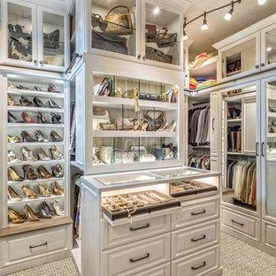 Foto di uno spazio per vestirsi per donna chic con ante bianche, moquette, pavimento beige e ante di vetro