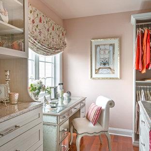 Diseño de vestidor de mujer, romántico, de tamaño medio, con armarios estilo shaker, puertas de armario blancas, suelo de madera en tonos medios y suelo marrón