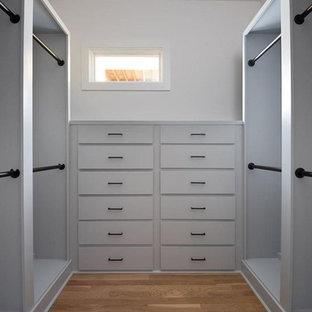 Modelo de vestidor unisex, minimalista, de tamaño medio, con armarios con rebordes decorativos, puertas de armario blancas, suelo de madera en tonos medios y suelo beige