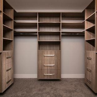 Imagen de armario vestidor unisex, actual, de tamaño medio, con armarios con paneles lisos, puertas de armario de madera oscura y moqueta