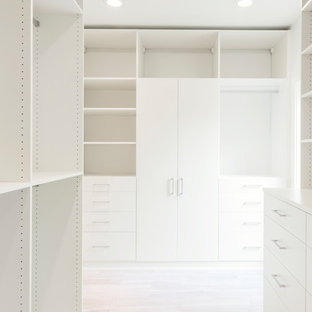 Large contemporary gender-neutral walk-in wardrobe in Dallas with limestone floors, beige floor, flat-panel cabinets and white cabinets.