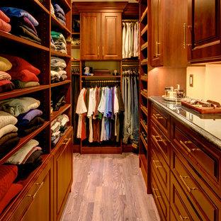 Ejemplo de armario vestidor de hombre, tradicional, de tamaño medio, con armarios con paneles con relieve, puertas de armario de madera en tonos medios, suelo de madera en tonos medios y suelo marrón