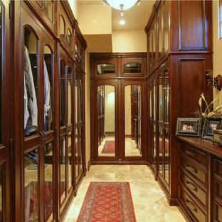 Modelo de vestidor de hombre, de estilo de casa de campo, extra grande, con armarios con paneles empotrados, puertas de armario de madera en tonos medios, suelo de travertino y suelo multicolor