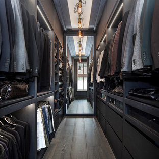 Inspiration for a large traditional walk-in wardrobe for men in London with flat-panel cabinets, black cabinets, dark hardwood flooring and brown floors.