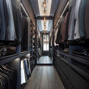Ejemplo de armario vestidor de hombre, clásico renovado, grande, con armarios con paneles lisos, puertas de armario negras, suelo de madera oscura y suelo marrón