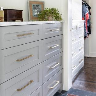 Inredning av en klassisk stor garderob, med skåp i shakerstil, vita skåp, skiffergolv och svart golv