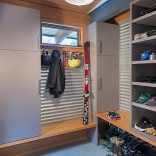 Aménagement d'un dressing et rangement contemporain de taille moyenne avec béton au sol, un placard à porte plane et des portes de placard grises.