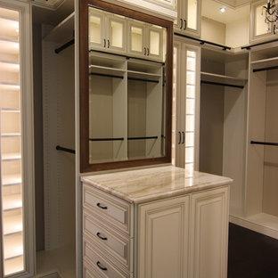 Imagen de armario vestidor clásico, grande, con armarios con paneles con relieve, puertas de armario beige, suelo de madera oscura y suelo marrón