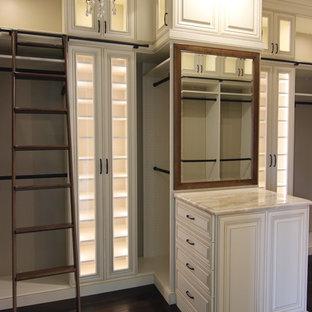 Modelo de armario vestidor tradicional, grande, con armarios con paneles con relieve, puertas de armario beige, suelo de madera oscura y suelo marrón