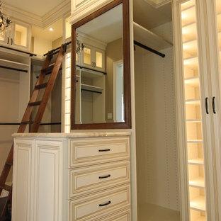 Ejemplo de armario vestidor clásico, grande, con armarios con paneles con relieve, puertas de armario beige, suelo de madera oscura y suelo marrón