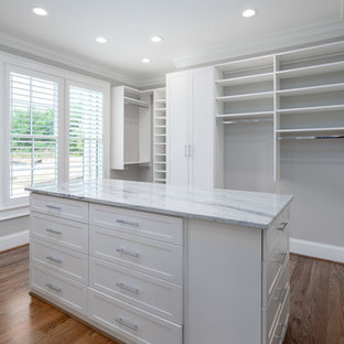 Photo of a large midcentury gender-neutral walk-in wardrobe in Other with open cabinets, white cabinets, medium hardwood floors and brown floor.