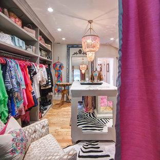 Ejemplo de vestidor de mujer, bohemio, de tamaño medio, con puertas de armario grises, suelo de madera en tonos medios y armarios abiertos