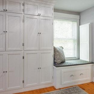 Diseño de armario y vestidor clásico, de tamaño medio, con armarios con paneles empotrados, puertas de armario grises, suelo de baldosas de porcelana y suelo blanco