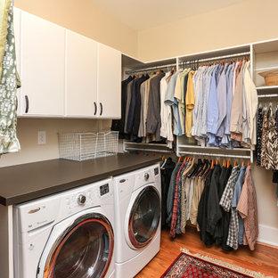 Idéer för mellanstora vintage walk-in-closets för könsneutrala, med släta luckor, vita skåp och mellanmörkt trägolv