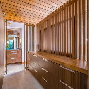 Ejemplo de armario vestidor unisex, moderno, de tamaño medio, con armarios con paneles lisos, puertas de armario de madera oscura, suelo de baldosas de cerámica y suelo gris