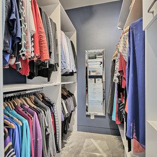 Foto de armario vestidor unisex, tradicional, pequeño, con armarios con paneles lisos, puertas de armario blancas y suelo de cemento
