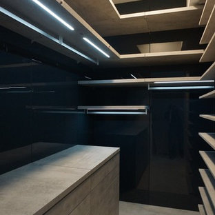 Immagine di una piccola cabina armadio unisex minimalista con nessun'anta e pavimento in cemento