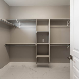 Example of a mid-sized classic gender-neutral ceramic floor and white floor walk-in closet design in Other