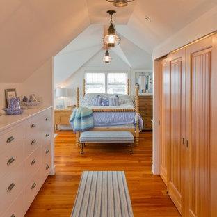 Mittelgroßer Maritimer Begehbarer Kleiderschrank mit weißen Schränken, braunem Holzboden und flächenbündigen Schrankfronten in Boston