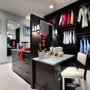 Foto di un grande spazio per vestirsi design con ante lisce, ante in legno bruno e moquette