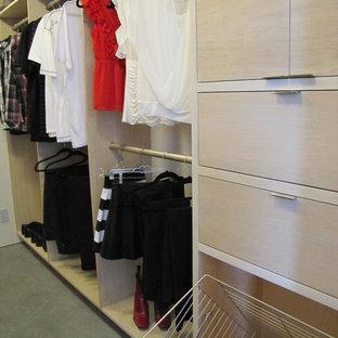 Diseño de armario vestidor unisex, actual, de tamaño medio, con armarios con paneles lisos, puertas de armario de madera clara y suelo de cemento