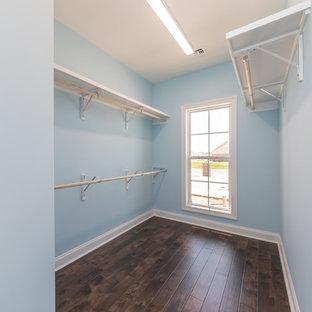Immagine di una cabina armadio unisex tradizionale di medie dimensioni con ante con bugna sagomata, pavimento in laminato e pavimento marrone