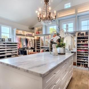 Diseño de armario vestidor de mujer, campestre, grande, con armarios estilo shaker, puertas de armario blancas, suelo de madera clara y suelo marrón