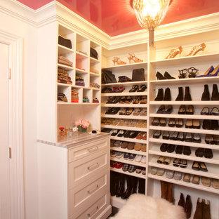 Diseño de armario vestidor de mujer, clásico, de tamaño medio, con armarios con paneles lisos, puertas de armario blancas y suelo de madera oscura