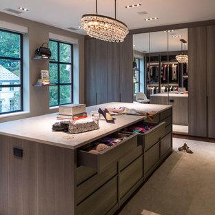 Ispirazione per un'ampia cabina armadio per donna design con ante lisce, ante in legno scuro, moquette e pavimento beige