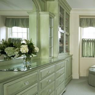Diseño de vestidor de mujer, tradicional, grande, con armarios con paneles con relieve, puertas de armario verdes, moqueta y suelo gris
