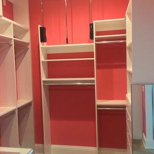 Foto de armario vestidor de mujer, moderno, grande, con armarios con paneles con relieve, puertas de armario blancas, suelo vinílico y suelo marrón