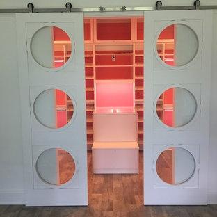 Immagine di una grande cabina armadio per donna moderna con ante con bugna sagomata, ante bianche, pavimento in vinile e pavimento marrone