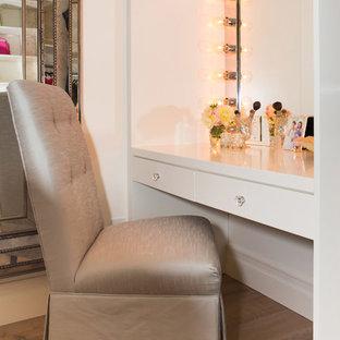 Foto de armario vestidor de mujer, mediterráneo, grande, con armarios con paneles con relieve, puertas de armario blancas y suelo de madera en tonos medios