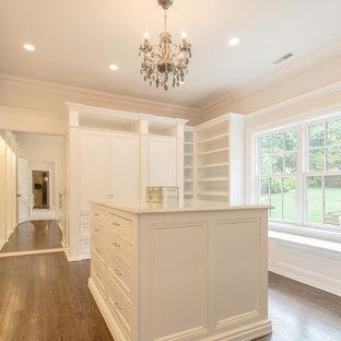 Imagen de armario vestidor de mujer, clásico, grande, con armarios con rebordes decorativos, puertas de armario blancas y suelo de madera clara
