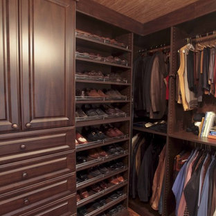 Example of a classic walk-in closet design in New Orleans with dark wood cabinets