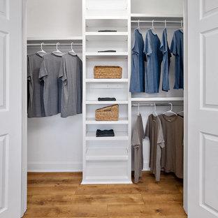 Immagine di un armadio o armadio a muro unisex tradizionale di medie dimensioni con pavimento in laminato, pavimento marrone, nessun'anta e ante bianche