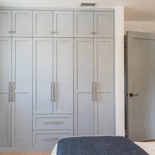 Imagen de armario unisex, costero, pequeño, con armarios estilo shaker, puertas de armario azules, suelo de madera en tonos medios y suelo marrón