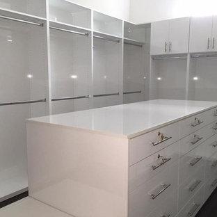 Modelo de armario vestidor unisex, contemporáneo, grande, con armarios con paneles lisos, puertas de armario blancas, suelo de madera oscura y suelo marrón