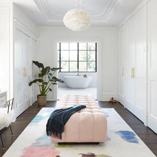 Modelo de vestidor unisex, clásico renovado, de tamaño medio, con armarios estilo shaker, puertas de armario blancas, suelo marrón y suelo de madera oscura