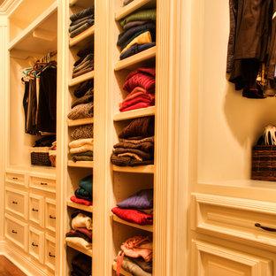 Foto de armario vestidor unisex, de estilo americano, con armarios con paneles con relieve, puertas de armario blancas y suelo de madera en tonos medios